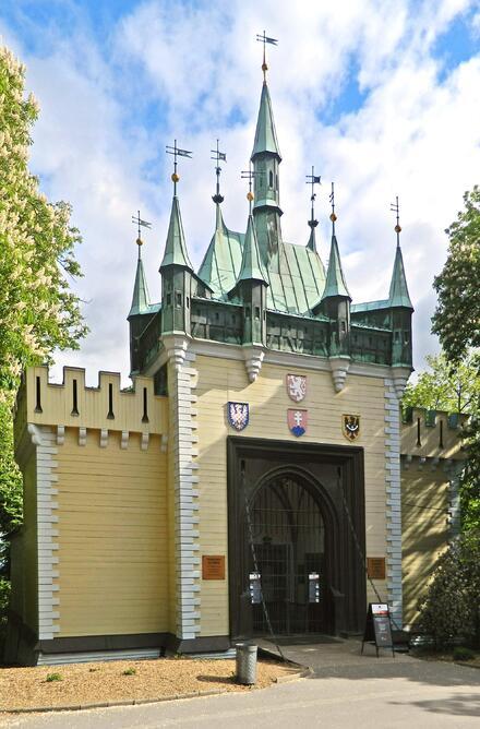 Vchod do Zrcadlového bludiště vypadá jako věž starobylého hradu s cimbuřím a korouhvemi.