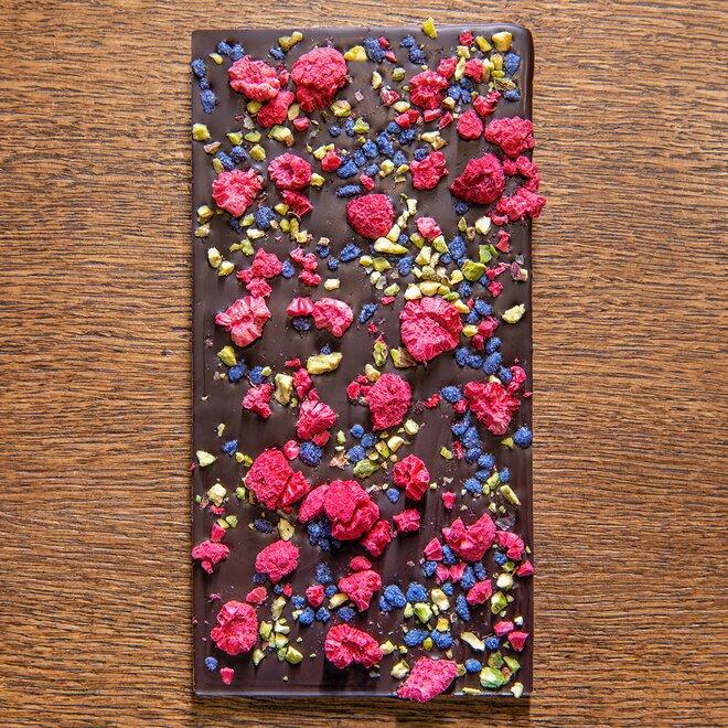 Hořká čokoláda s 68 % kakaa zdobená sekanými pistáciemi, fialkami v cukru a malinami