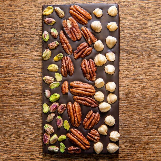 Hořká čokoláda s 68 % kakaa zdobená pistáciemi, lískovými a pekanovými ořechy
