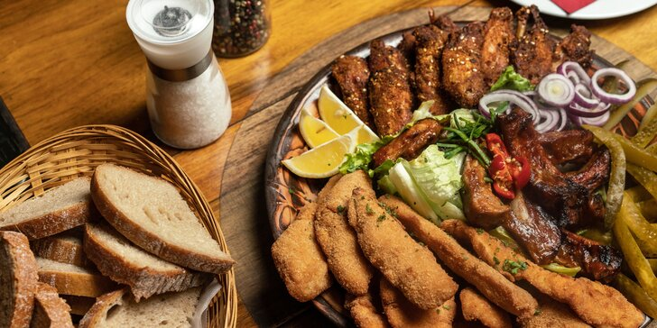 Talíř plný masa v moderní restauraci: kuřecí křídla, vepřová žebra i smažené řízky