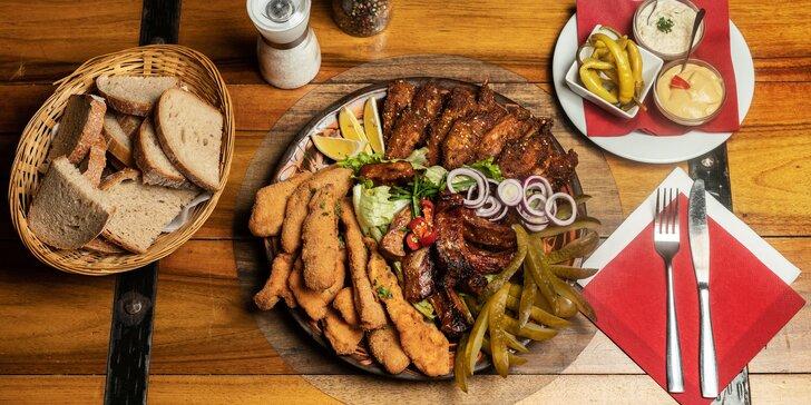 Talíř plný masa ve stylové restauraci: kuřecí křídla, vepřová žebra i smažené řízky