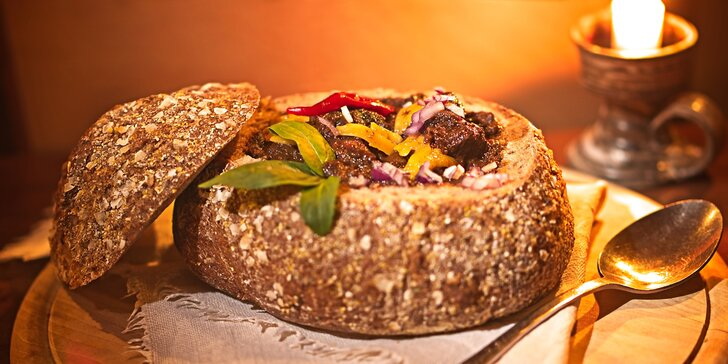 Pikantní guláš v chlebu sypaný cheddarem v restauraci plné pivních speciálů